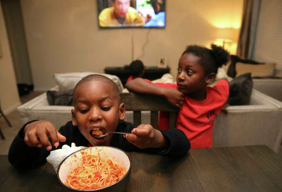 Lavell Thomas, 4, eats spaghetti for dinner as his cousin Kasie Clewis, 5, watches at their new apartment Friday, Nov. 10, 2017, in Stafford. Lavell and his mother Charde Wilson had to be rescued from the flood waters when Hurricane Harvey hit their Meyerland apartment. They moved into this new partment about a month ago. ( Yi-Chin Lee / Houston Chronicle ) Photo: Yi-Chin Lee, Staff / © 2017 Houston Chronicle