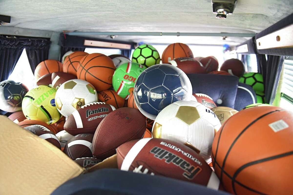 Volunteers help unload a van full of sports balls as CruisinO for Tots delivers toys at the Niskayuna District 1 Fire Department Stuff the Truck event on Saturday, Nov. 25, 2017 in Niskayuna, N.Y. Members of Bad Moon Riders MC, ABATE Albany NY chapter, American Legion Post 1092 and TS PicArt raised $5,000 on a fundraiser Dutch Apple Cruise in August.They partnered with Five Below in September to buy footballs, basketballs, soccer balls and seven shopping carts of toys for girls of all ages.(Lori Van Buren / Times Union)