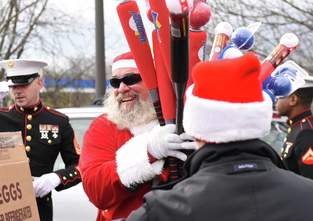Tim Bliss is dressed as Santa Claus helps unload toys as CruisinO for Tots delivers toys at the Niskayuna District 1 Fire Department Stuff the Truck event on Saturday, Nov. 25, 2017 in Niskayuna, N.Y. Members of Bad Moon Riders MC, ABATE Albany NY chapter, American Legion Post 1092 and TS PicArt raised $5,000 on a fundraiser Dutch Apple Cruise in August.They partnered with Five Below in September to buy footballs, basketballs, soccer balls and seven shopping carts of toys for girls of all ages.(Lori Van Buren / Times Union)