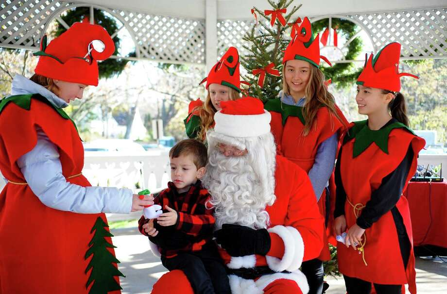 Santa's elf Aggie Michalska, 12, at left, gives a gift to Christopher Belletzkie, 3, of Fairfield, as he visits with Santa on the Sherman Green in Fairfield, Conn., on Saturday Nov. 25, 2017. Photo: Christian Abraham / Hearst Connecticut Media / Connecticut Post