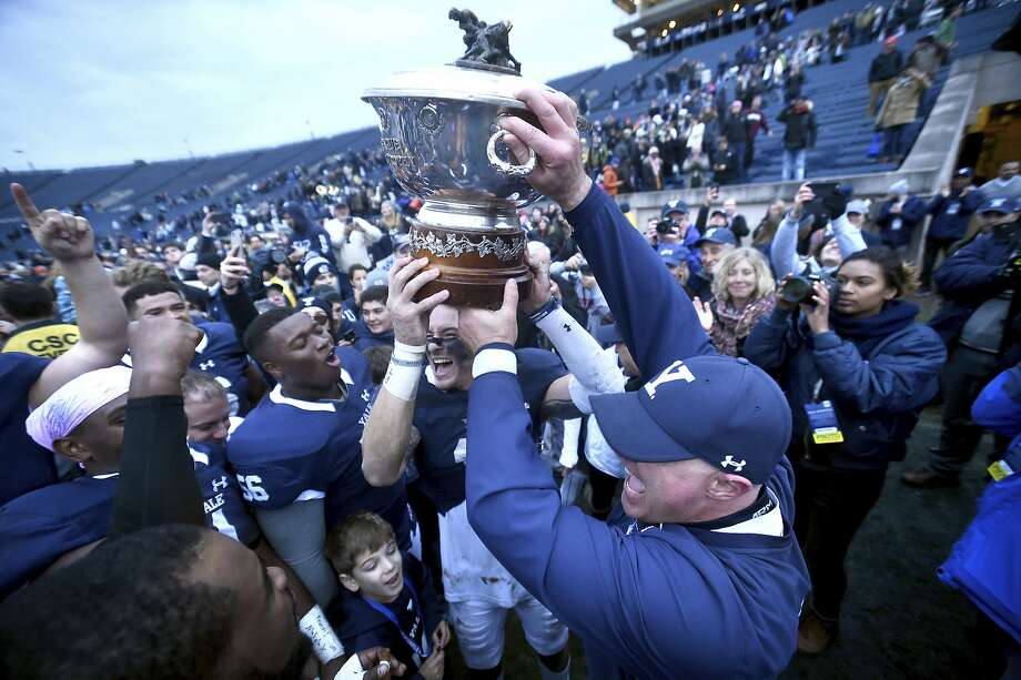 Yale's Spencer Rymiszewski, center, and head coach Tony Reno hold up the Ivy League Football Trophy after their win against Harvard in an NCAA college football game on Saturday, Nov. 18, 2017 in New Haven, Conn. Yale won 24-3, securing the Bulldogs' first outright Ivy League championship in 37 years. (Arnold Gold/New Haven Register via AP) Photo: Arnold Gold, Associated Press