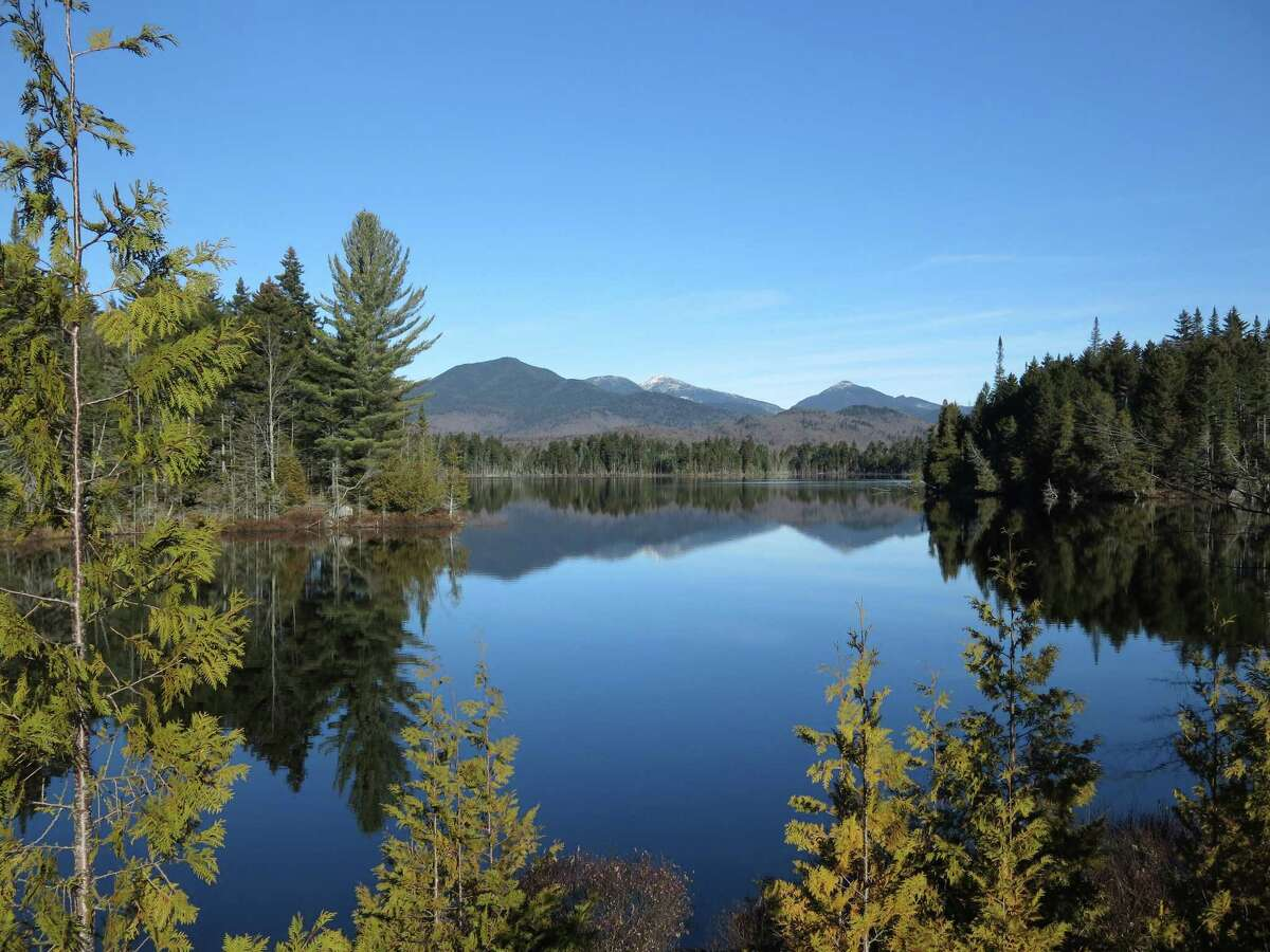 The Adirondack High Peaks, including snow-capped Mount Marcy, the state's highest summit, rear center, are reflected in Boreas Pond in North Hudson, N.Y. (AP Photo/Mary Esch, File)