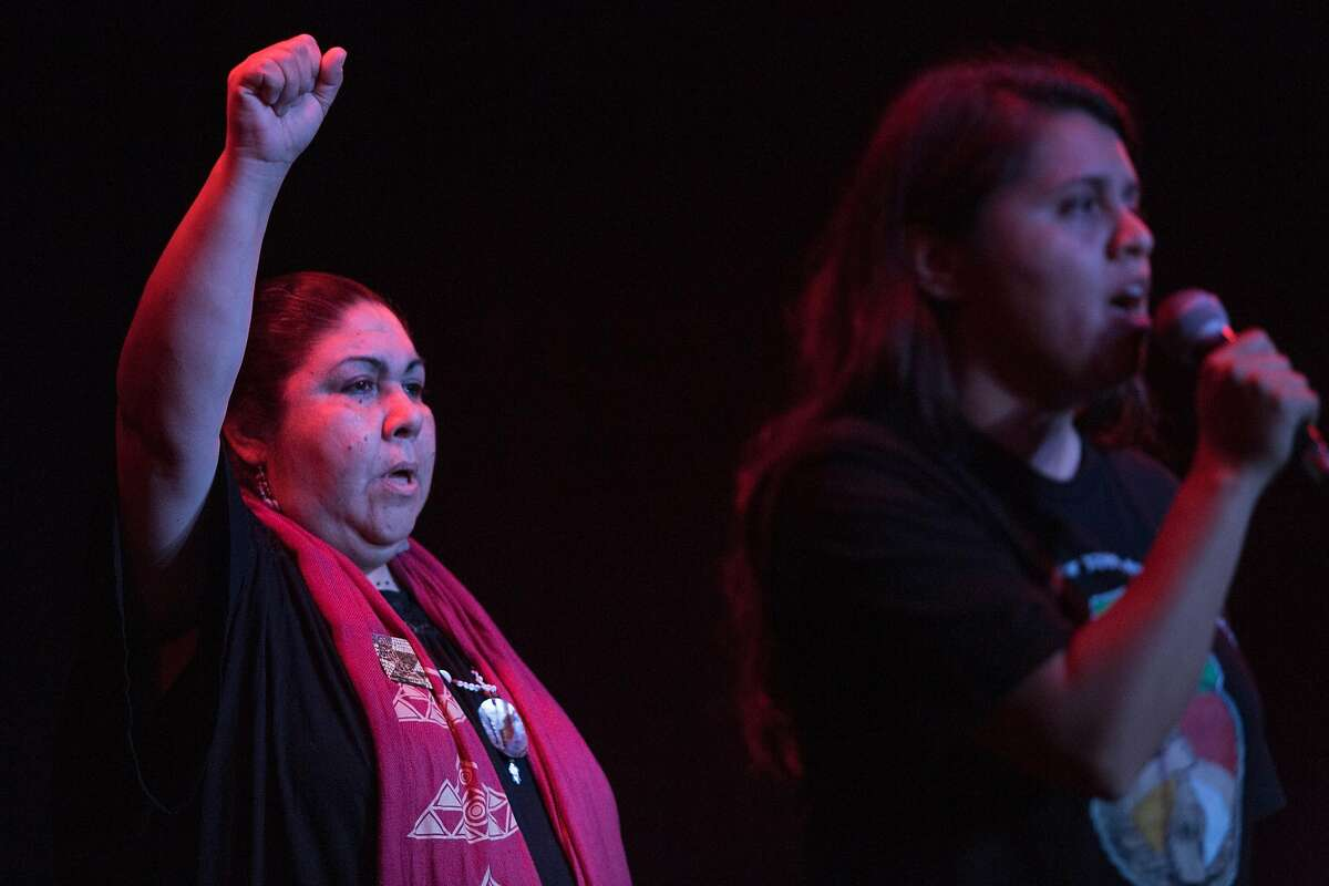 Corinna Gould, left, raises her hand while her neice, Desirae Harp, sings during