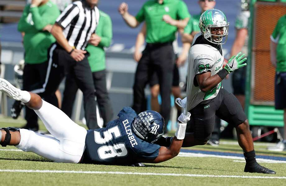 North Texas running back Nic Smith, right, eludes the tackle attempt of Rice linebacker Emmanuel Ellerbee in the first half. Smith carried 26 times for 178 yards. Photo: Karen Warren, Staff / © 2017 Houston Chronicle