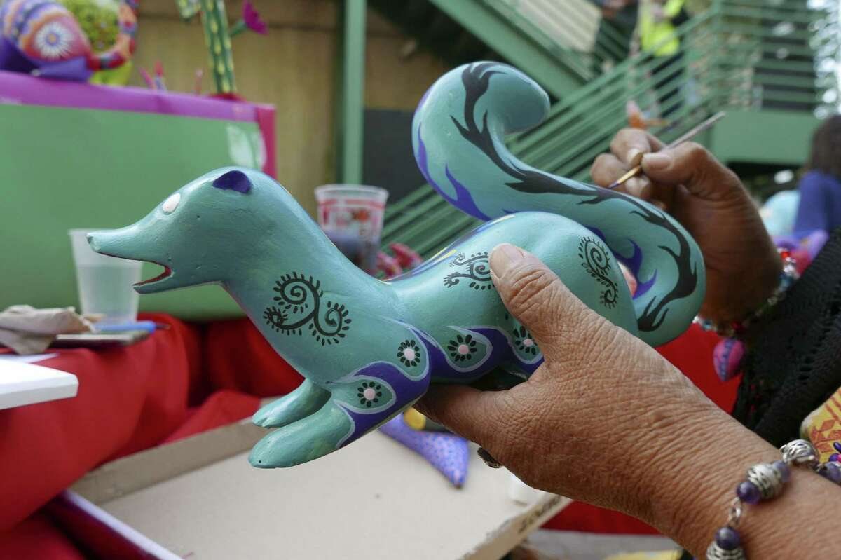 Cristina Antonio Herrera, who is from the municipality of Arrazolaxoxo in the Mexican state of Oaxaca, paints an alebrije, a kind of fantasy creature, at the annual International Peace Market at the Esperanza Peace and Justice Center on Saturday, Nov. 25, 2017. The event is in its 28th year. It combines arts and social consciousness economic sustainability. It is touted as a place to buy unique Christmas gifts. Herrera's home was damaged in a recent earthquake.