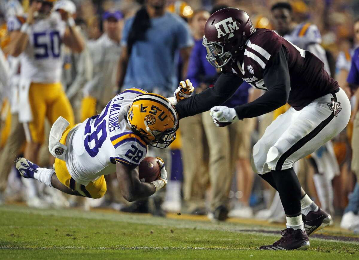 Texas A&M defensive lineman Landis Durham tackles LSU running back Darrel Williams (28) during the first half of an NCAA college football game in Baton Rouge, La., Saturday, Nov. 25, 2017. (AP Photo/Gerald Herbert)