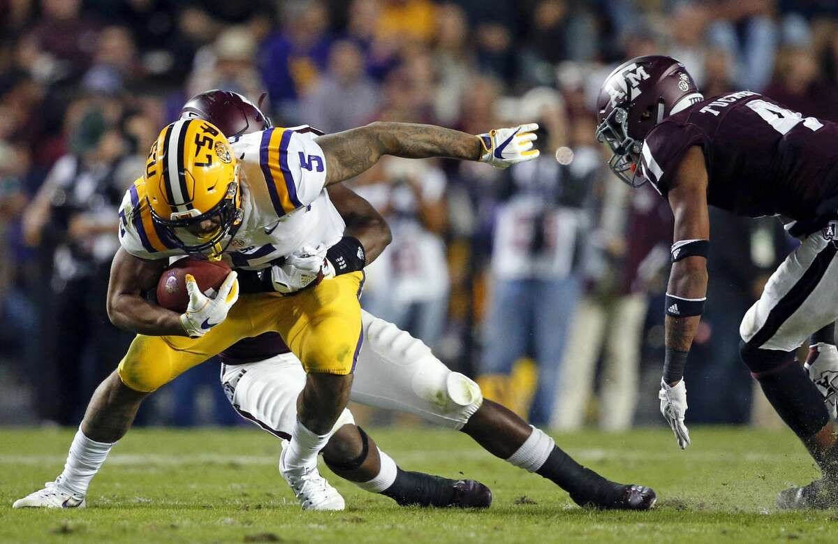 LSU running back Derrius Guice (5) is tackled by Texas A&M linebacker Keeath Magee II as defensive back Derrick Tucker (4) closes in, during the first half of an NCAA college football game in Baton Rouge, La., Saturday, Nov. 25, 2017. (AP Photo/Gerald Herbert)