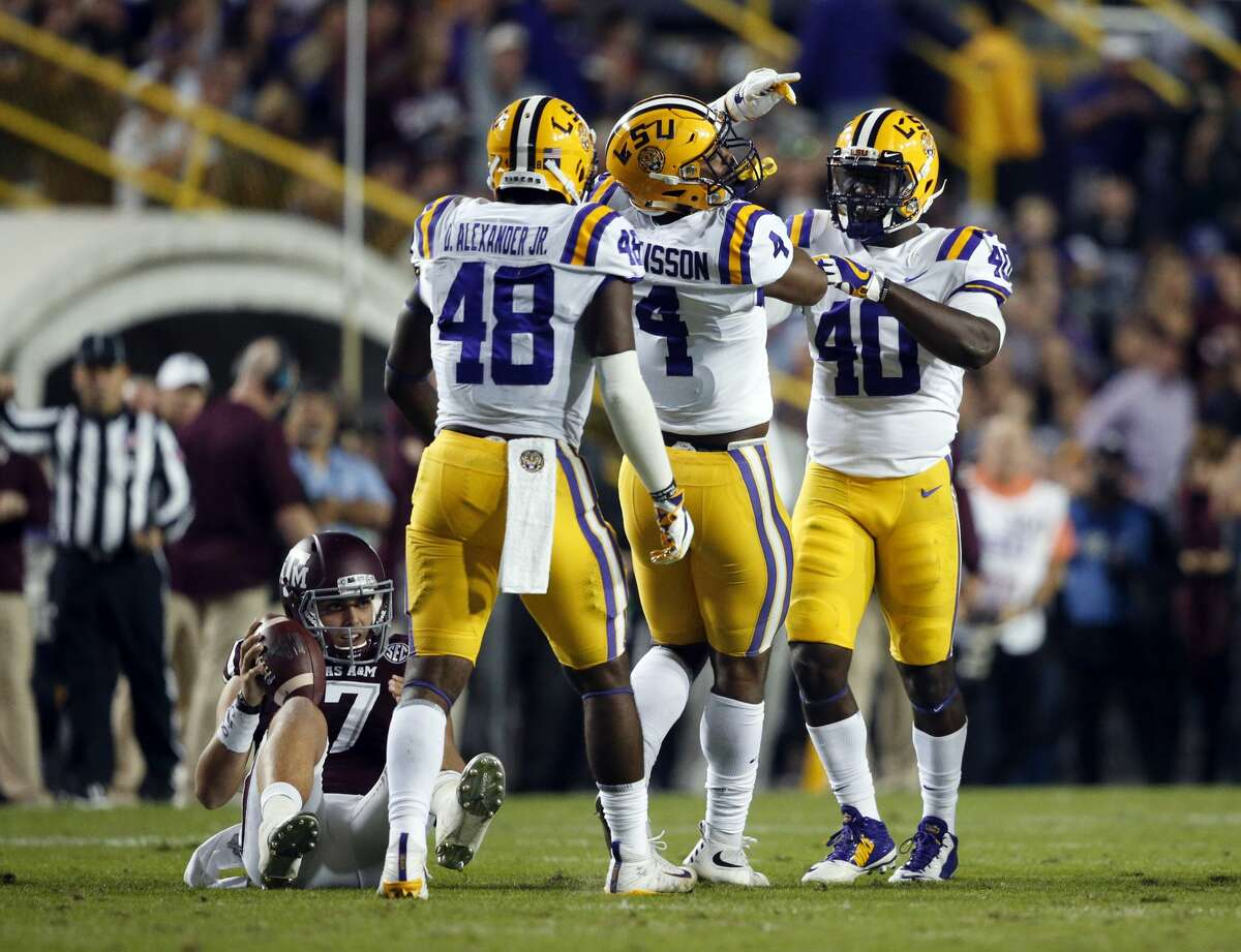 LSU linebackers Donnie Alexander (48), K'Lavon Chaisson (4) and Devin White (40) celebrate a sack as Texas A&M quarterback Nick Starkel (17) sits on the turf during the first half of an NCAA college football game in Baton Rouge, La., Saturday, Nov. 25, 2017. (AP Photo/Gerald Herbert)