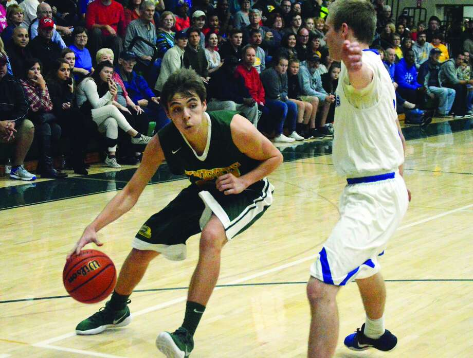 Metro-East Lutheran guard Jonah Odgen, left, drives against Alton Marquette's Sammy Green in third-quarter action in the championship game of the MELHS Turkey Tip-Off Classic.