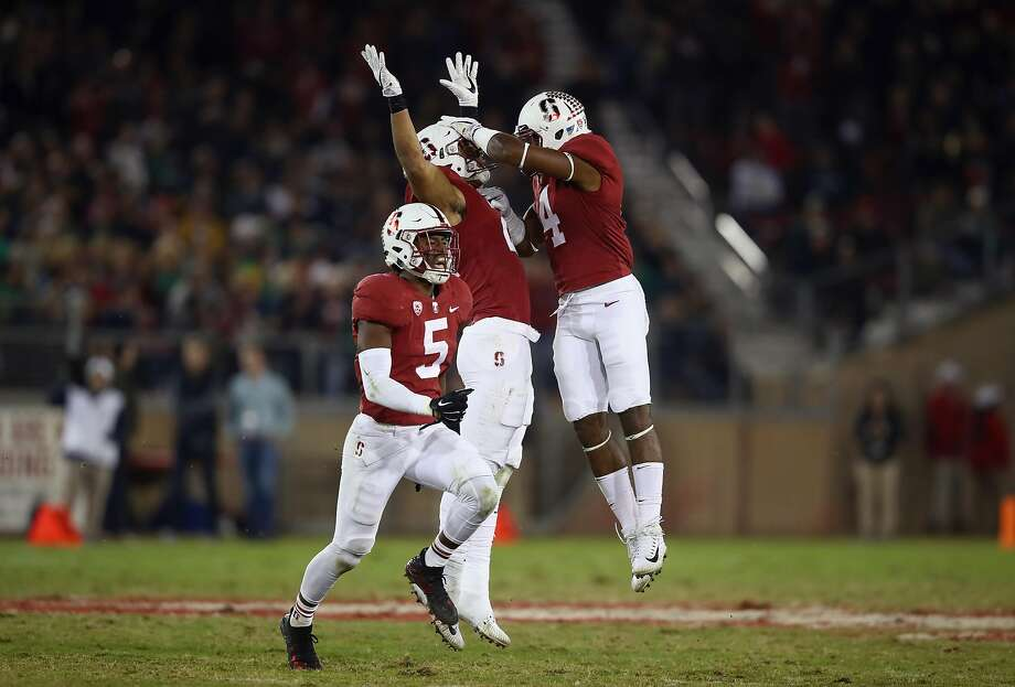 Curtis Robinson #21 of the Stanford Cardinal celebrates with Alameen Murphy #4 and Frank Buncom #5 after Robinson intercepted a pass against the Notre Dame. The Cardinal won the Pac-12 North title. Photo: Ezra Shaw, Getty Images