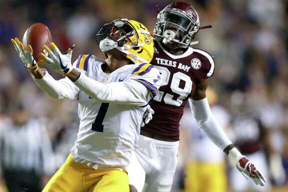 LSU's D.J. Chark catches a pass as Texas A&M's Debione Renfro defends during the first half at Tiger Stadium in Baton Rouge, La., on Saturday night.