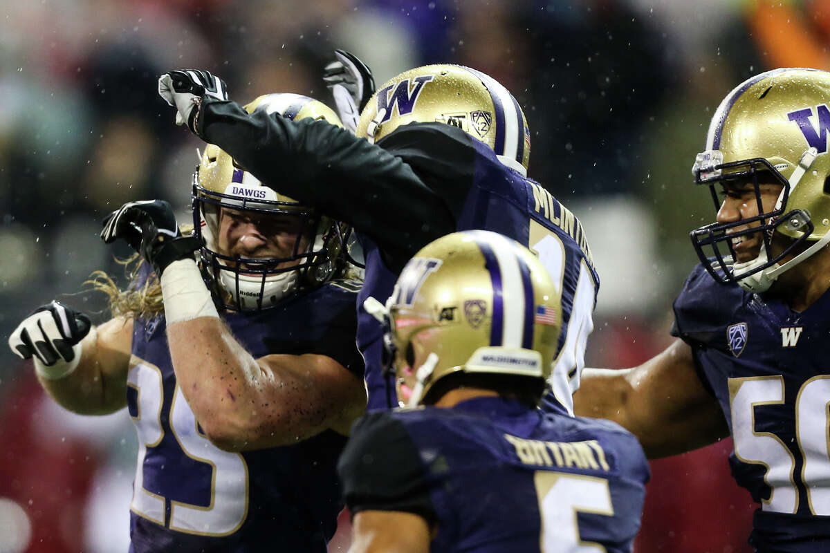 Washington's Ben Burr-Kirven celebrates his interception during the second half of the Apple Cup at Husky Stadium on Saturday, Nov. 25, 2017.
