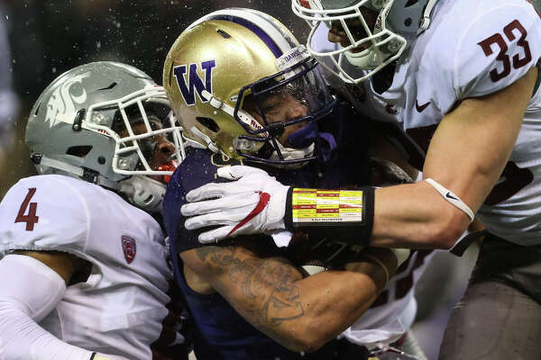Washington State defensive back Marcus Strong and linebacker Dylan Hanser hit Washington tail back Myles Gaskin during the second half of the Apple Cup at Husky Stadium on Saturday, Nov. 25, 2017.
