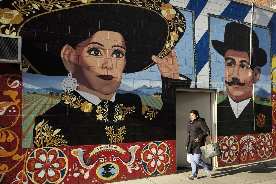 A Boston mural depicts Veronica Robles, a community activist who moved to the city from Mexico in 2000, and Carmello Scire, a catering entrepreneur who arrived in the city from Italy in the 1930s. Photo: Steven Senne, Associated Press