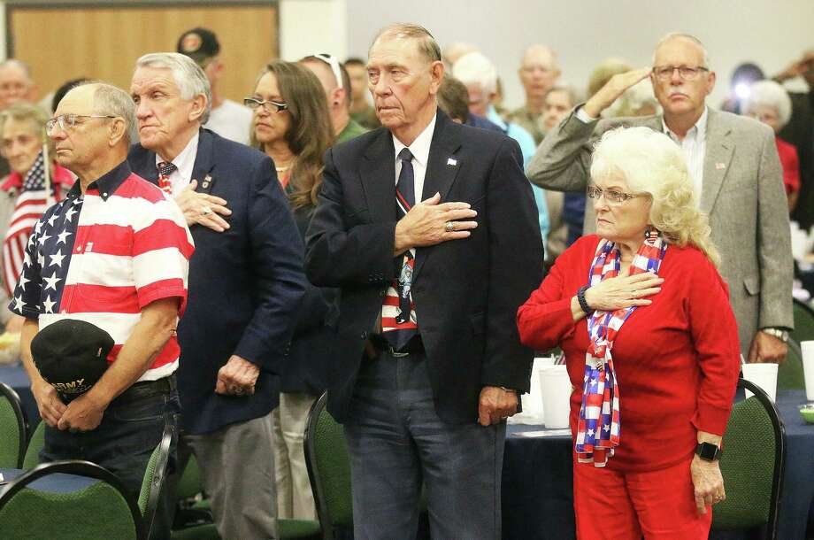 Veterans, their families and guests place their hands over their heart during the somber playing of Taps at the annual Dayton Veterans Luncheon at the Dayton Community Center. Photo: David Taylor