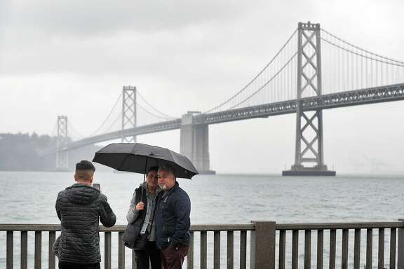 Emraan Azimi, 17, left, takes a photo of his parents, David and Zari on the Embarcadero in San Francisco, Calif., Sunday, November 26, 2017, as a storm dropped several inches of rain throughout the bay