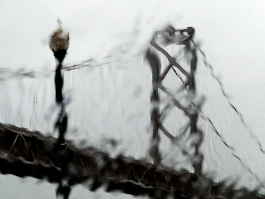 The westernmost tower of the Bay Bridge is seen through runny rain drops on the Embarcadero in San Francisco, Calif., Sunday, November 26, 2017, as a storm dropped several inches of rain throughout the bay Photo: Carlos Avila Gonzalez / The Chronicle