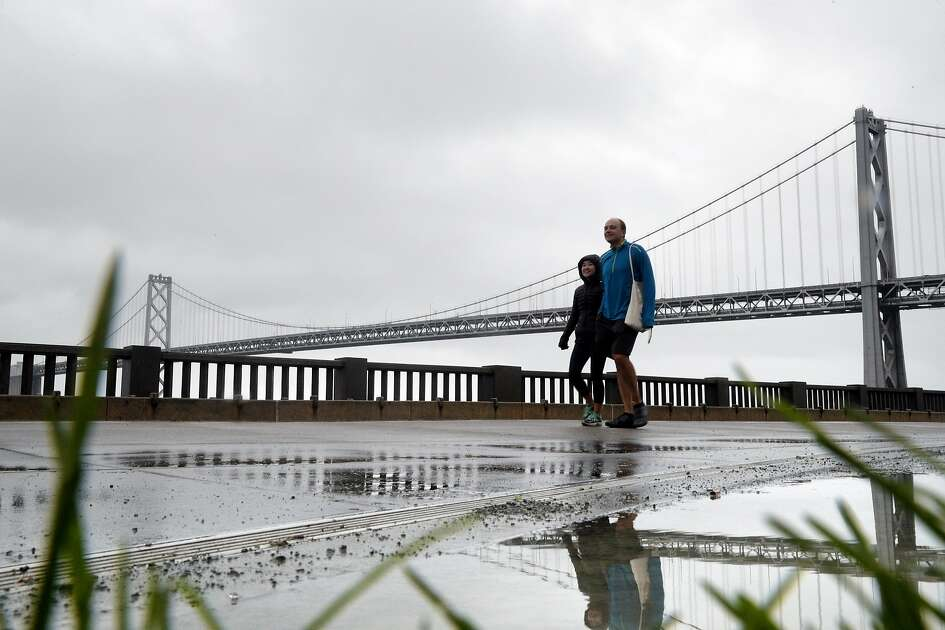A couple walks along the soggy Embarcadero in San Francisco, Calif., Sunday, November 26, 2017, as a storm dropped several inches of rain throughout the bay