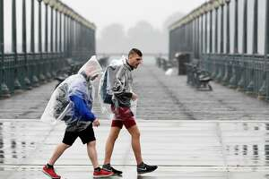 Pedestrians keep dry wearing plastic ponchos on the Embarcadero in San Francisco, Calif., Sunday, November 26, 2017, as a storm dropped several inches of rain throughout the bay