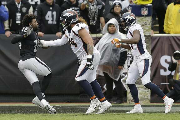 Oakland Raiders wide receiver Michael Crabtree, left, fights with Denver Broncos nose tackle Domata Peko, center, and cornerback Aqib Talib during the first half of an NFL football game in Oakland, Calif., Sunday, Nov. 26, 2017. Crabtree and Talib were ejected. (AP Photo/Ben Margot)