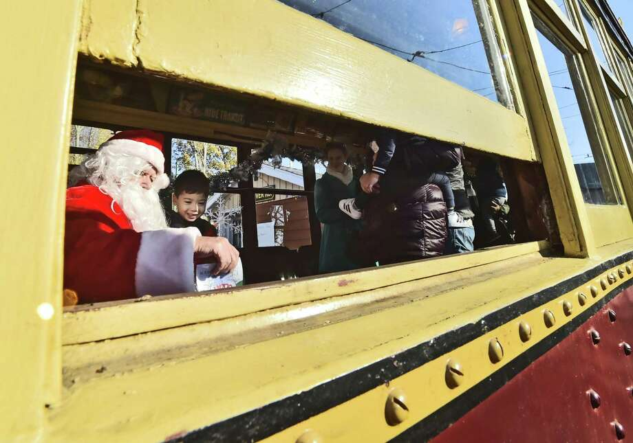 East Haven, Connecticut - Saturday, November 25, 2017:  Santa Claus, on a visit to the Shore Line Trolley Museum in East Haven Saturday, left, gives Evan Lai, 3, of Dobbs Ferry, N.Y., a small gift during Santa's Wonderland celebration Saturday at the museum. Besides taking a ride on a trolley, guests to the museum enjoy a complimentary cookie and hot chocolate with an added bonus of getting a look at a model train layout at the oldest continuously running suburban trolley line in the USA operated by the Branford Electric Railway Association. Photo: Peter Hvizdak / Hearst Connecticut Media / New Haven Register