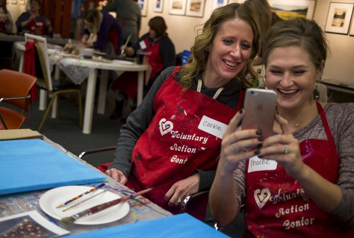Jennifer Dymora of Albee Township smiles as she poses for a selfie with Lauren Herline of Midland, right, during the Cocktails and Canvas event held at Creative 360 on Saturday, Nov. 25, 2017. Attendees spent the evening painting one of two designs as a leader provided instruction. (Josie Norris/for the Daily News)