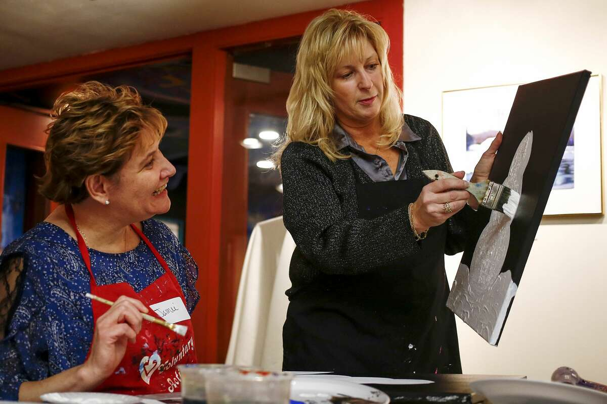 Ursula Steckert of Saginaw Township, right, shows Jamie Flory of St. Charles how to paint a snowman during the Cocktails and Canvas event held at Creative 360 on Saturday, Nov. 25, 2017. Attendees spent the evening painting one of two designs as a leader provided instruction. (Josie Norris/for the Daily News)
