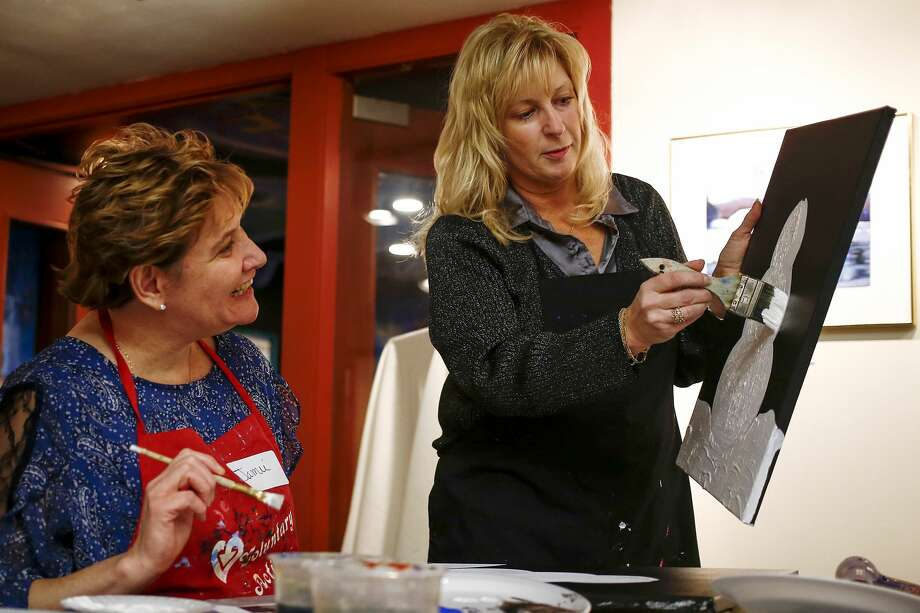 Ursula Steckert of Saginaw Township, right, shows Jamie Flory of St. Charles how to paint a snowman during the Cocktails and Canvas event held at Creative 360 on Saturday, Nov. 25, 2017. Attendees spent the evening painting one of two designs as a leader provided instruction. (Josie Norris/for the Daily News) Photo: (Josie Norris/for The Daily News)
