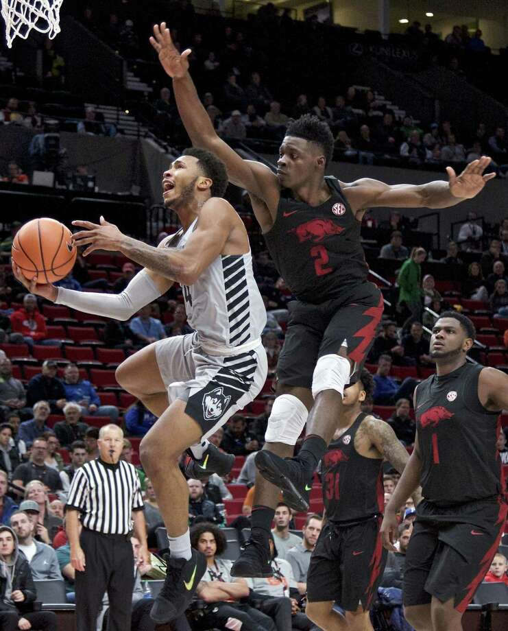 UConn guard Jalen Adams, left, shoots past Arkansas forward Adrio Bailey during the first half of their Phil Knight Invitational tournament game in Portland, Ore., on Sunday. Arkansas won 102-67. Photo: Craig Mitchelldyer / Associated Press / FR170751 AP