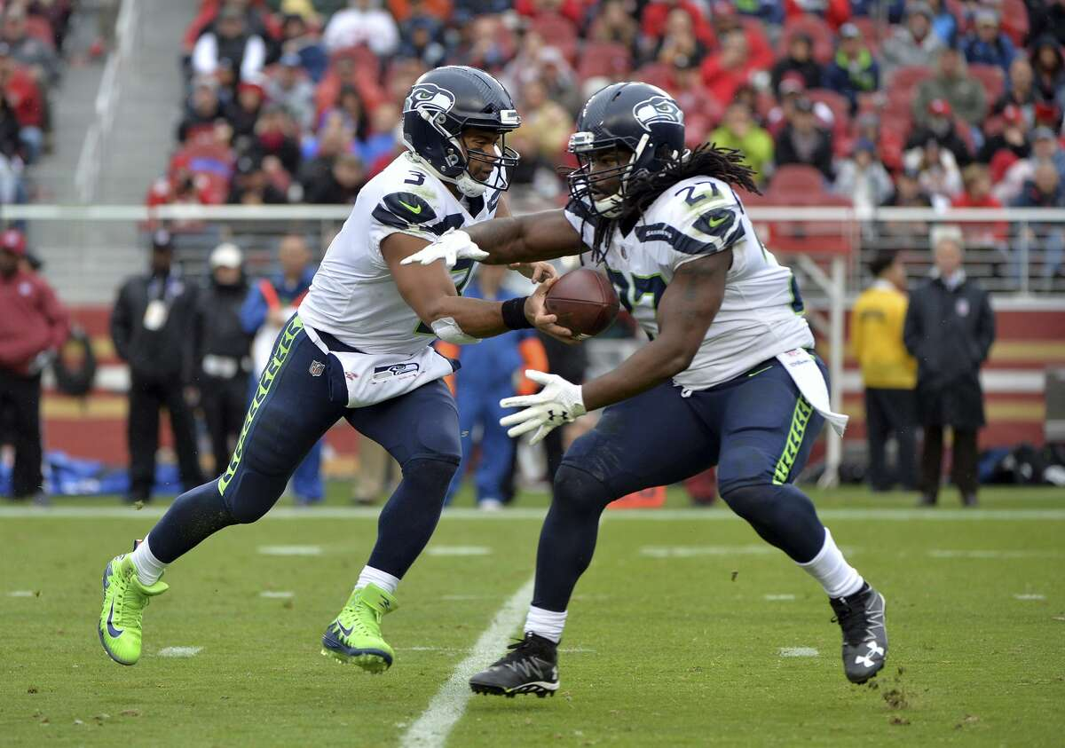 Seattle Seahawks quarterback Russell Wilson (3) hands off to running back Eddie Lacy (27) during the first half of an NFL football game against the San Francisco 49ers Sunday, Nov. 26, 2017, in Santa Clara, Calif. (AP Photo/Don Feria)
