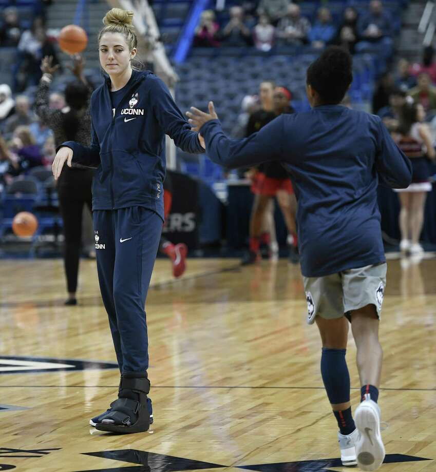 UConn's Katie Lou Samuelson, left wears a boot on her left foot as she slaps hands with teammate Crystal Dangerfield before the first half against Maryland on Nov. 19 in Hartford. Photo: Jessica Hill / Associated Press / AP2017