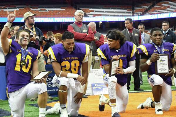 Troy players from left to right: Matt Ashley, Luis Virola, Dev Holmes, and Joey Ward kneel following receiving their MVP awards of the Class AA State Football Championship at the Carrier Dome on Sunday in Syracuse. Troy claimed the state title for the second consecutive year by beating Lancaster 41-26. (Jenn March, Special to the Times Union) ORG XMIT: 112717_hsfb
