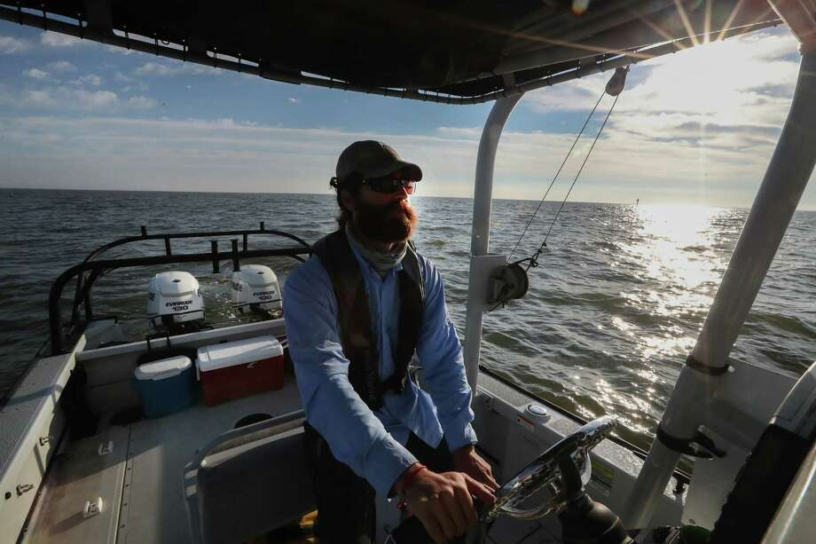 Biologist Cory Scanes pilots a boat in Galveston Bay, where dolphins are turning up with skin lesions. Photo: Steve Gonzales, Houston Chronicle / © 2017 Houston Chronicle