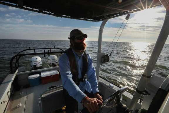 Biologist Cory Scanes pilots a boat in Galveston Bay, where dolphins are turning up with skin lesions.