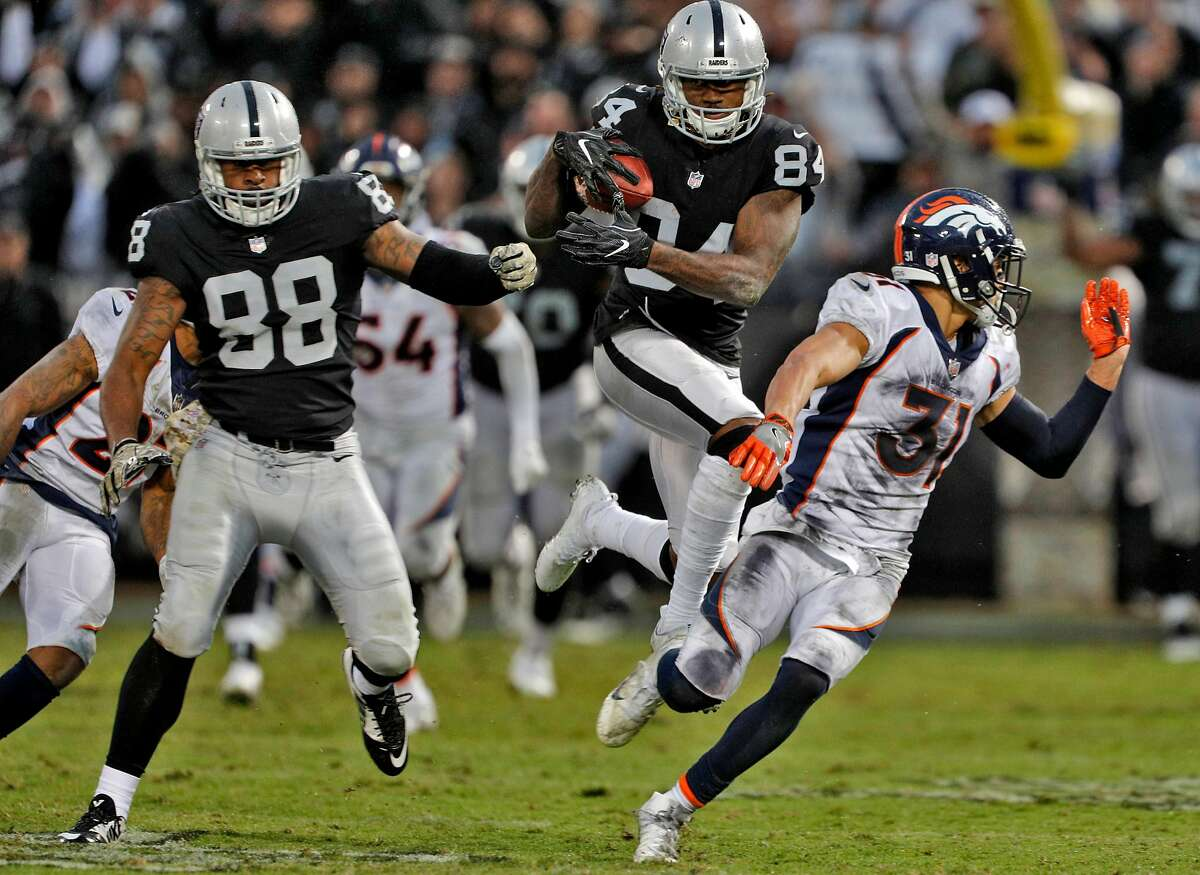 Cordarrelle Patterson (84) leaps to get around defenders as he runs after a 52-yard pass from Derek Carr (4) in the final minutes of the game as the Oakland Raiders played the Denver Broncos at the Oakland Coliseum in Oakland, Calif., Sunday, November 26, 2017. The Raiders defeated the Broncos 21-14.