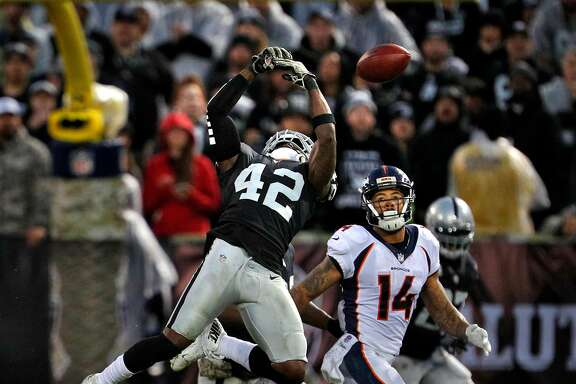 Karl Joseph (42) can't quite make the catch on a pass intended from Trevor Siemian (13) to Cody Latimer (14) who completed the catch in the fourth quarter as the Oakland Raiders played the Denver Broncos at the Oakland Coliseum in Oakland, Calif., Sunday, November 26, 2017. The Raiders defeated the Broncos 21-14.