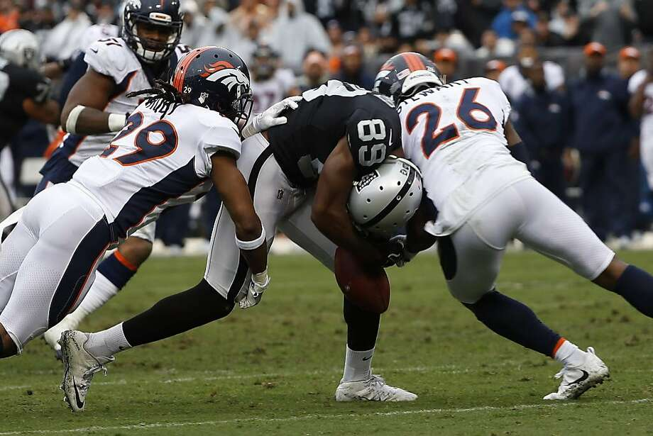 OAKLAND, CA - NOVEMBER 26: Amari Cooper #89 of the Oakland Raiders drops the ball as he is hit by Darian Stewart #26 and Bradley Roby #29 of the Denver Broncos during the during the second quarter of his NFL football game against the Denver Broncos at Oakland-Alameda County Coliseum on November 26, 2017 in Oakland, California. (Photo by Stephen Lam/Getty Images) Photo: Stephen Lam, Getty Images