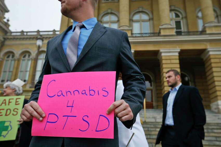 FILE - In this Tuesday, April 7, 2015, file photo, a Marine veteran holds a sign to show support for cannabis for post traumatic stress disorder sufferers, outside the State Capitol in Des Moines, Iowa. (Michael Zamora/The Des Moines Register via AP) ORG XMIT: IADES201