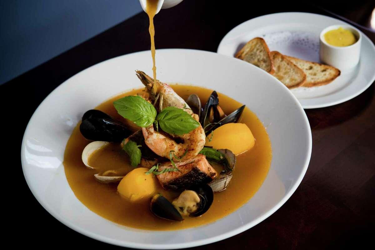 Bouillabaisse where the tomato-saffron fish broth is poured tableside at Maison Pucha Bistro.