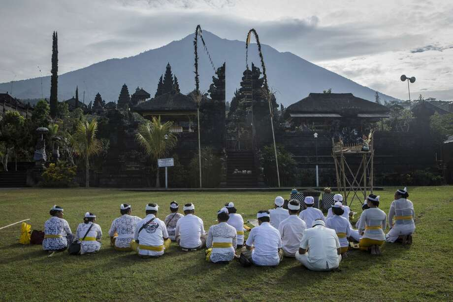 KARANGASEM, BALI, INDONESIA - SEPTEMBER 24: Balinese hindu worshipers pray at Besakih temple who in danger zones as mount Agung is seen on the background on September 24, 2017 in Karangasem regency, Island of Bali, Indonesia. Indonesian authorities raised the alert level for the Mount Agung volcano to the highest level as up to 30,000 villagers around the mountain evacuated their homes and travel warnings have been issued for the popular tourist destination. (Photo by Ulet Ifansasti/Getty Images) Photo: Ulet Ifansasti/Getty Images