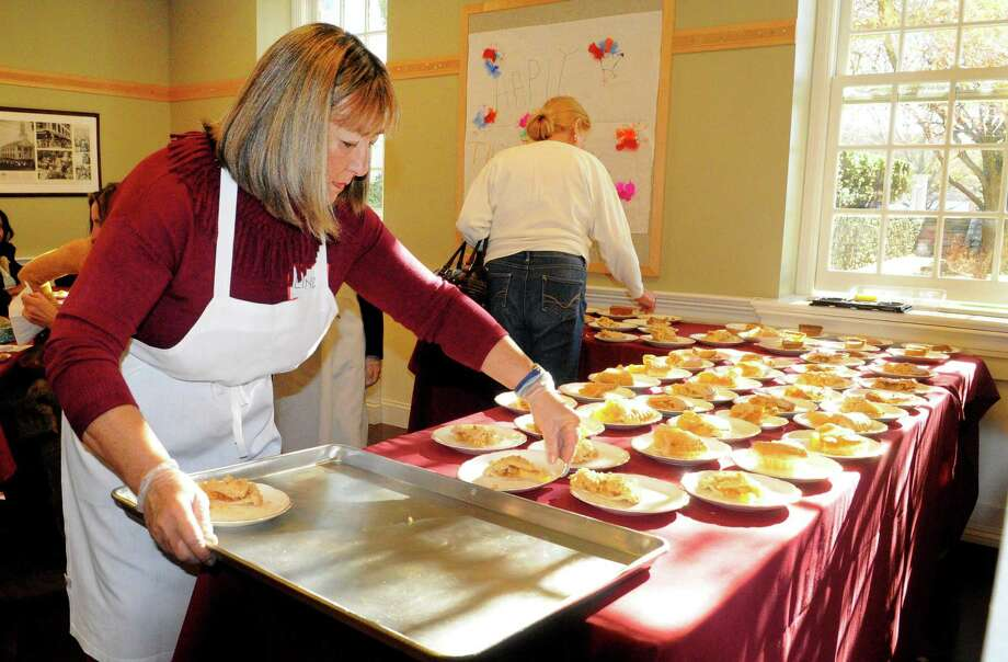 "Volunteer Linda Dimeglio, of Westport, puts out desserts for Saugatuck Congregational Church's 47th Annual Community Thanksgiving Feast in Westport, Conn., on Thursday Nov. 23, 2017. According to the church's website, ""For over 40 years, Saugatuck has been holding Community events on Thanksgiving and Christmas Day that are free and open to everyone – young families, homeless people, older folks, anyone who might otherwise be alone."" For more information on attending or volunteering go to: http://saugatuckchurch.org/ Photo: Christian Abraham / Hearst Connecticut Media / Connecticut Post"