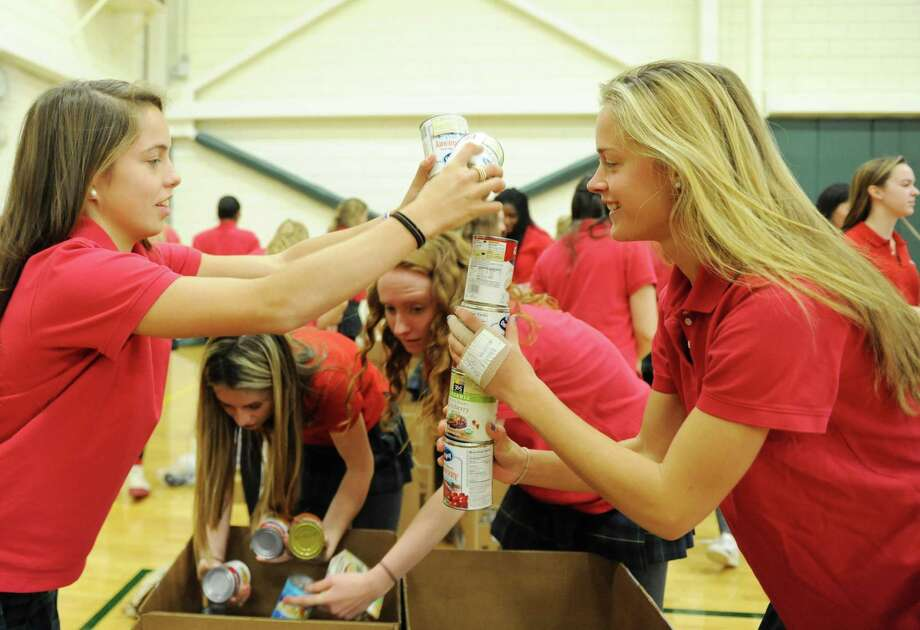 Seniors Sofi Viola, left, and Karina Schulze organize and balance donated canned goods at the annual Ingathering at Greenwich Academy on Tuesday. Photo: Tyler Sizemore / Hearst Connecticut Media / Greenwich Time