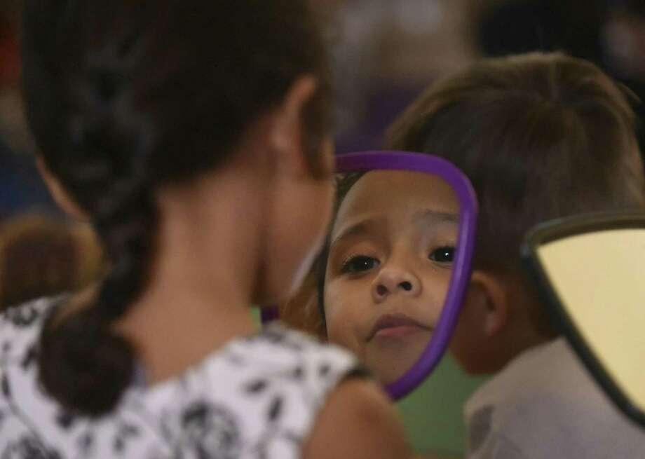 Lailah Gonzalez looks at herself in a mirror at the Pre-K 4 SA North Education Center on Feb. 28. Photo: Billy Calzada /San Antonio Express-News / San Antonio Express-News