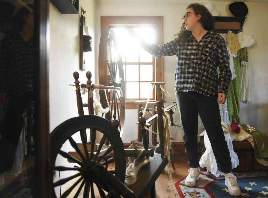 GHS student Miriam Ojjeh, 16, shows spinning wheels in the new upstairs children's area during the historic open house at Putnam Cottage/Knapp's Tavern in Greenwich, Conn. Sunday, Nov. 26, 2017. Docents led tours of the cottage, explaining the details of its vibrant history to curious attendees. There was also a new child-friendly portion of the cottage unveiled with popular Colonial games and toys, allowing kids to get a hands-on experience. Photo: Tyler Sizemore / Hearst Connecticut Media / Greenwich Time