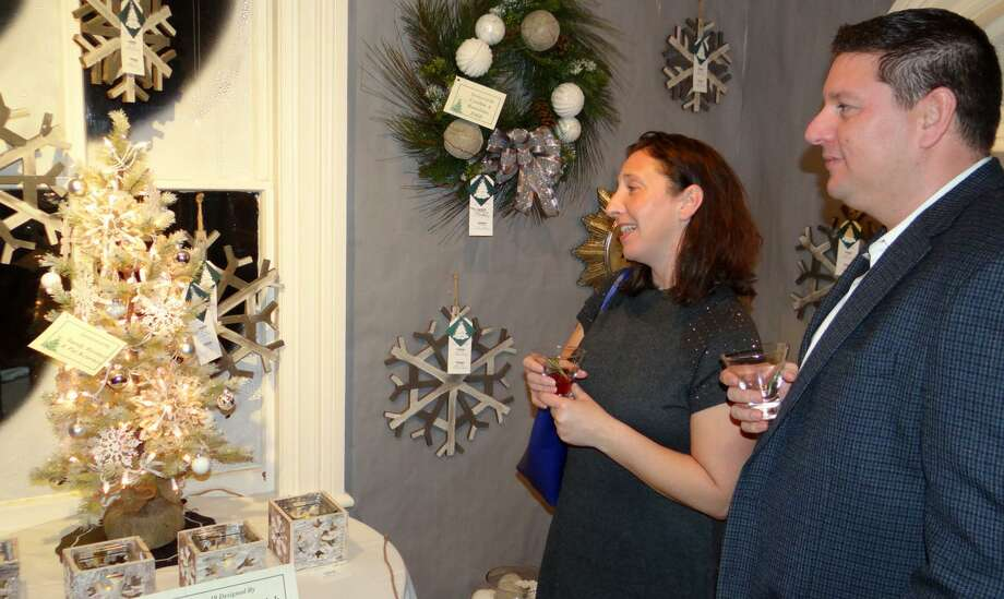 Visitors admire the decor at a previous Fairfield Christmas Tree Festival. This year's event runs Nov. 30 through Dec. 3 at the historic Burr Homestead. Photo: Mike Lauterborn / For Hearst Connecticut Media / Fairfield Citizen