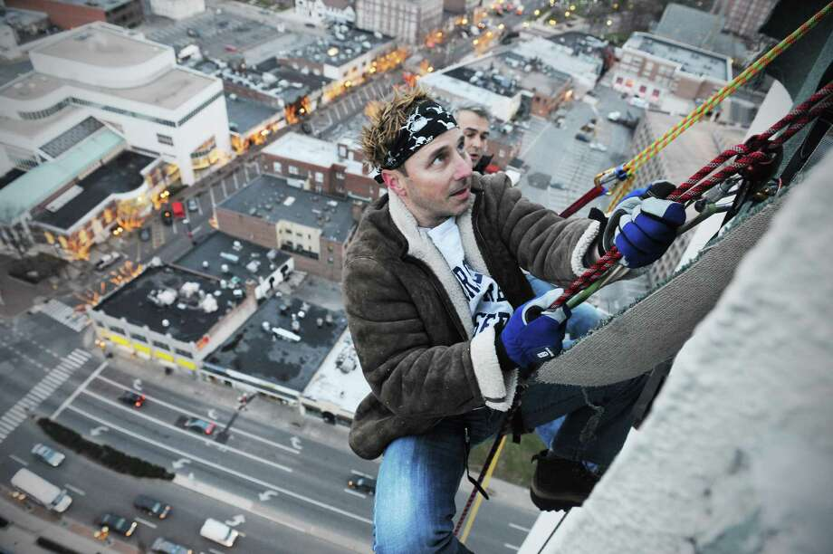 Brian Cashman, the New York Yankees general manager, rappels off the 350-foot Landmark Square in preparation for Sunday's 'Heights and Lights' celebration in Stamford on Friday.  Behind Cashman is climber Brian Van Orsdel. Photo: Kathleen O'Rourke / ST / Stamford Advocate