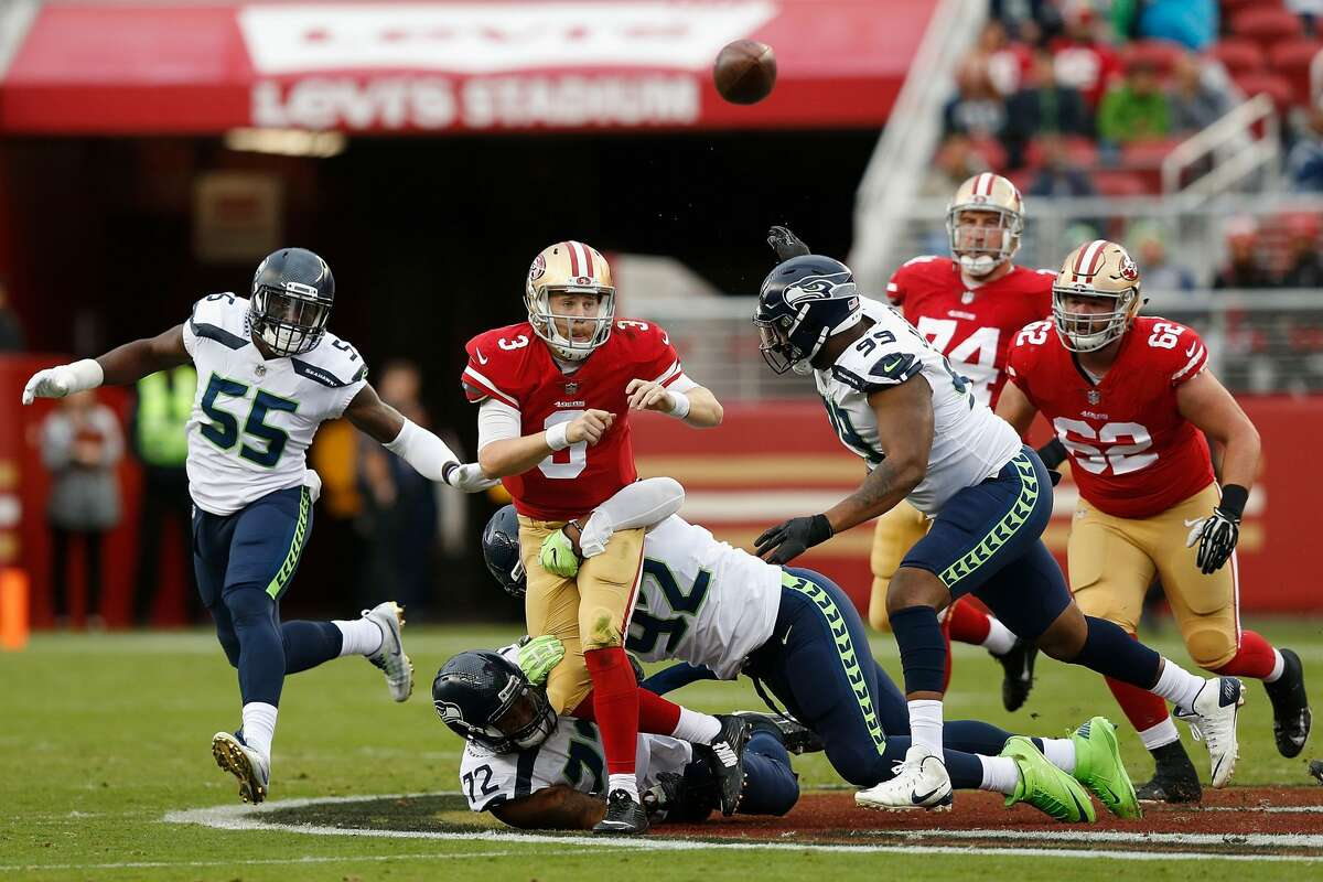 FILE-- C.J. Beathard #3 of the San Francisco 49ers is tackled by Michael Bennett #72 and Nazair Jones #92 of the Seattle Seahawks at Levi's Stadium on November 26, 2017 in Santa Clara, Calif.On the Sunday after Thanksgiving, Sacramento resident Tracy Mapes drove to Santa Clara, flew a drone over Levi's Stadium and dropped a payload of leaflets espousing his conspiracy theories over the San Francisco 49ers-Seattle Seahawks game.