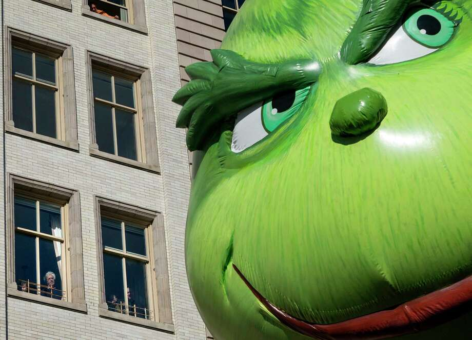The Grinch balloon passes by windows of a building on Central Park West during Macy's Thanksgiving Day Parade in New York Thursday, Nov. 23, 2017. (AP Photo/Craig Ruttle) ORG XMIT: NYCR116 Photo: Craig Ruttle, AP / FR61802 AP