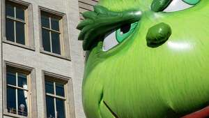 The Grinch balloon passes by windows of a building on Central Park West during Macy's Thanksgiving Day Parade in New York Thursday, Nov. 23, 2017. (AP Photo/Craig Ruttle) ORG XMIT: NYCR116