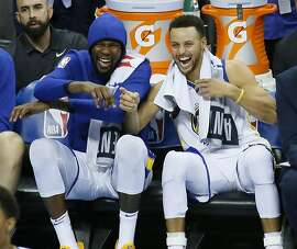 Golden State Warriors forward Kevin Durant, left, and guard Stephen Curry, right, laugh on the bench in the third quarter of an NBA basketball game as they lose to the Oklahoma City Thunder in Oklahoma City, Wednesday, Nov. 22, 2017. Oklahoma City won 108-91. (AP Photo/Sue Ogrocki)